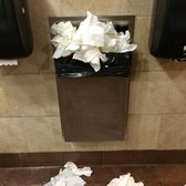 Unsanitary bathroom with trash can overflowing with paper towels and    Overflowing Trash Can