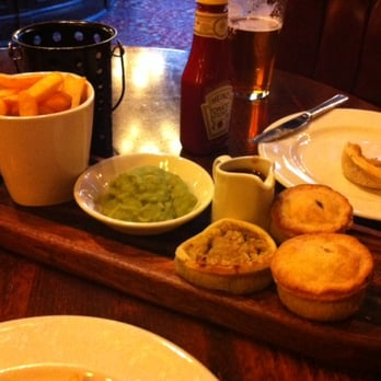 Selection of pies, peas, and chips.