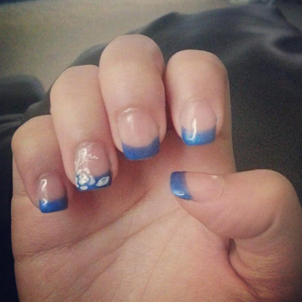 Dark blue french tip nails with a rose on the ring finger for 33 fingers salon