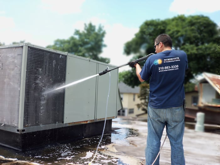 Hvac Technician Performing Coil Cleaning On A Rtu In
