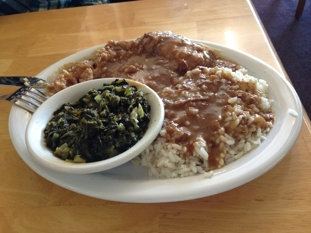 ... Smothered pork chop with rice and collard greens. Notice gravy over