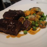 braised salt marsh lamb neck fillet with herb gnocchi, peas and carrots.