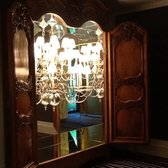 Exactly one half of a chandelier cleverly placed in a mirror lined antique armoire....