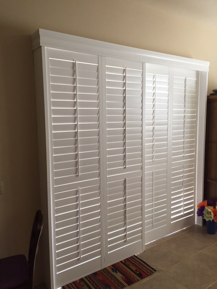 White Plantation Shutters Over A Sliding Door With Open