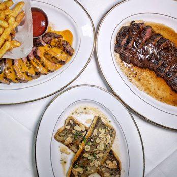 Photo of Boucherie West Village - New York, NY, United States. Steak au poivre (NY strip), truite aux amandes (trout), onglet du boeuf à la lyonnaise (hanger steak)