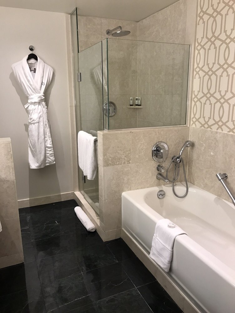 Bathroom with rain style shower head and fluffy robes. - Yelp