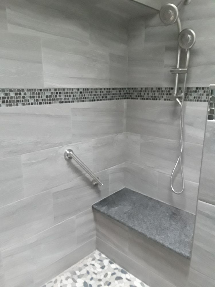 Porcelain tile shower with mosaic tile accent strip and a solid ...