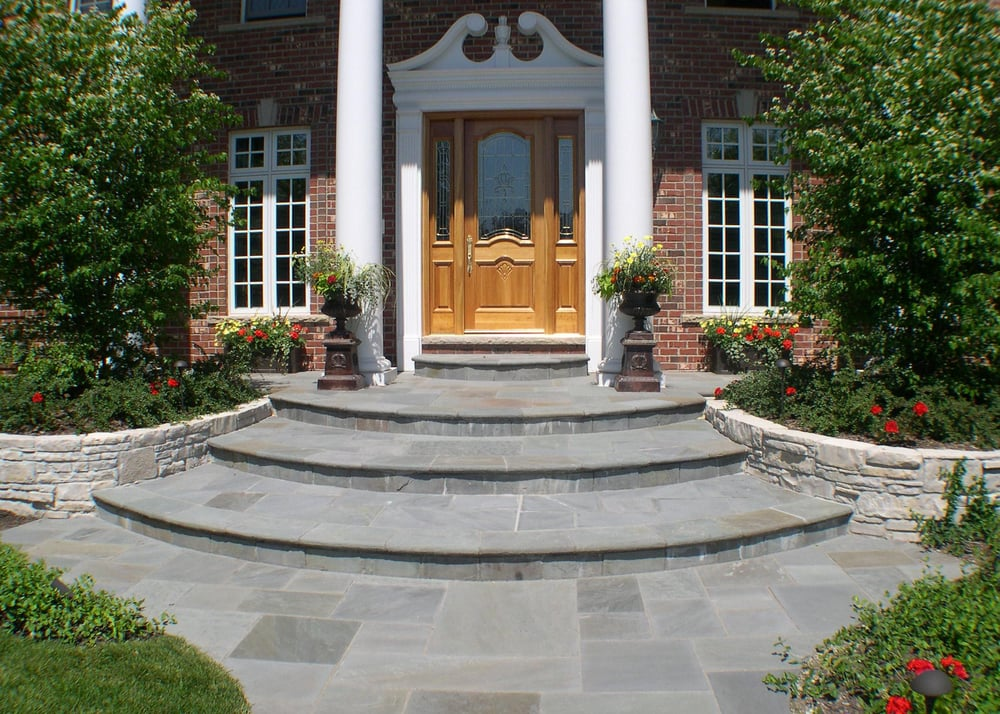 The curved natural stone walls support the radius for Bluestone front porch