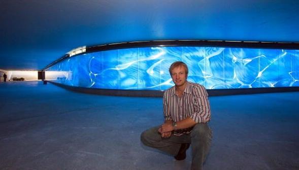 Osnabrücker Künstler vor seiner wand mit wasserflüsse simulierendem licht der