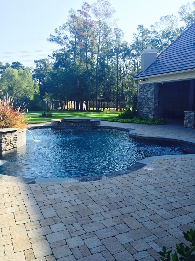 Backyard Paradise: Freeform Pool With Belgard Paver Deck, And Raised Wall
