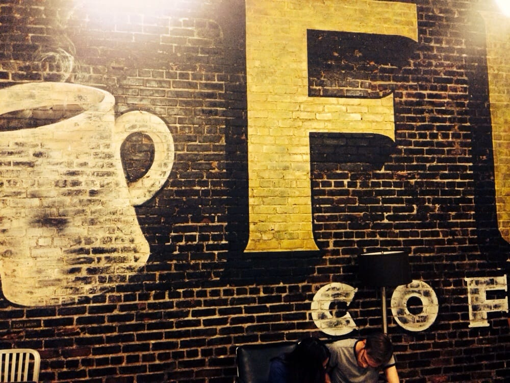 Awesome faux ghost sign on exposed brick wall in back room - Yelp