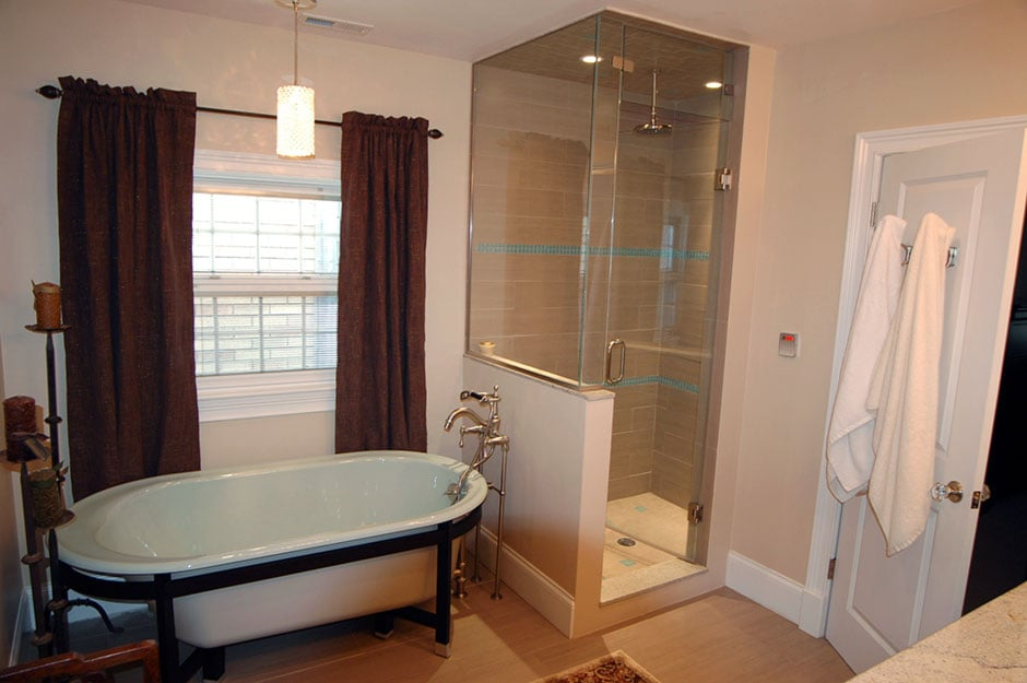 A bathroom featuring a clawfoot tub, glass-enclosed tile shower and ...