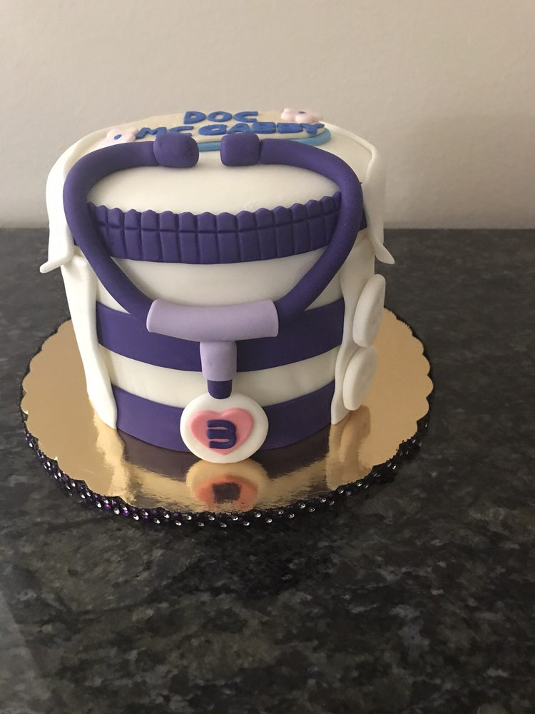 Cute Doc Mcstuffins Cake Decorated With A White Lab Coat Purple
