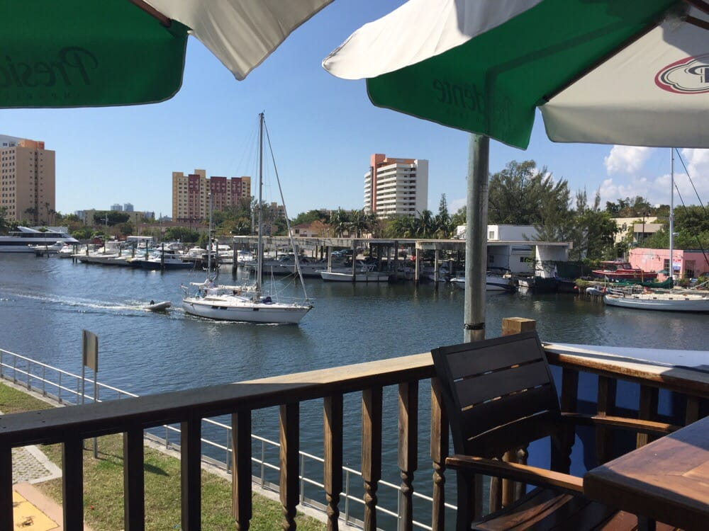 Outdoor dining enjoying the boats on the miami river for Fish market miami