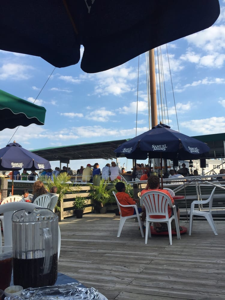 Sitting on the deck near the raw bar Facing the schooner - Yelp