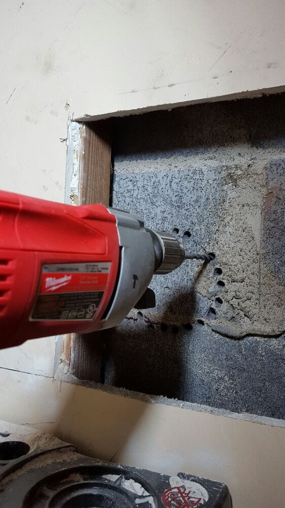 Drilling hole in concrete block wall for dryer vent pipe at