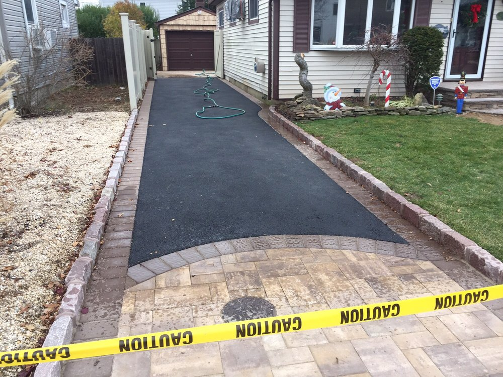 Blacktop driveway with Cambridge paver apron and borders done in