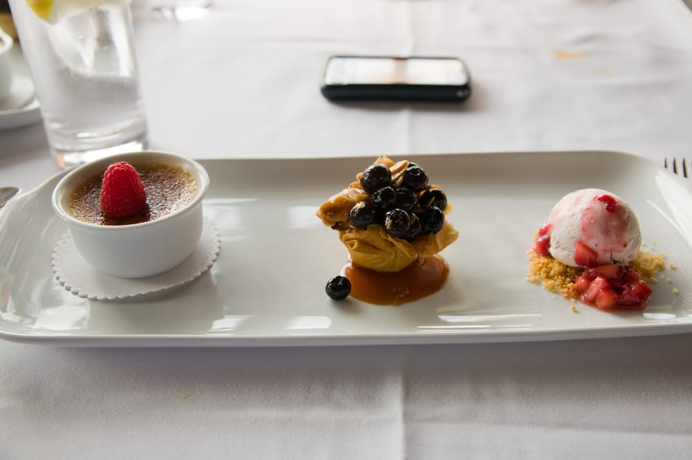Dessert trio - Creme Brulee, a blueberry tart, and a scoop ...