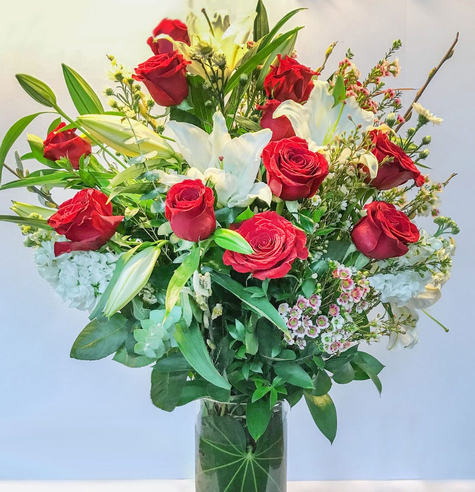 An Over The Top Arrangement Of A Dozen Red Roses With White Lilies