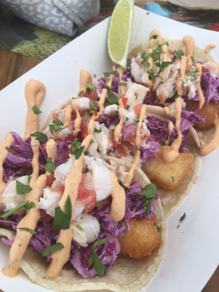 Halibut tacos topped with slaw chipotle crema and halibut for Good fish tacos near me