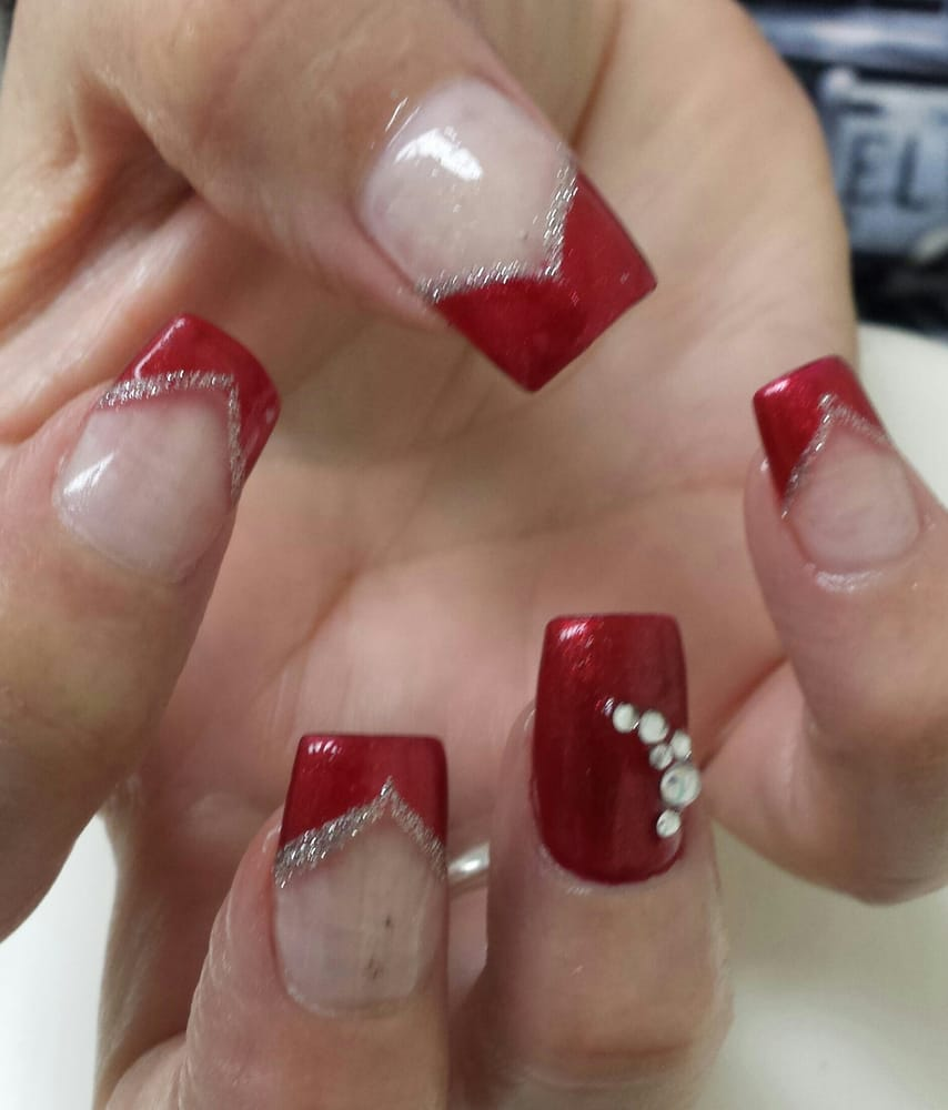 Square shaped acrylic nails, v-shaped red polish on tips with silver ...