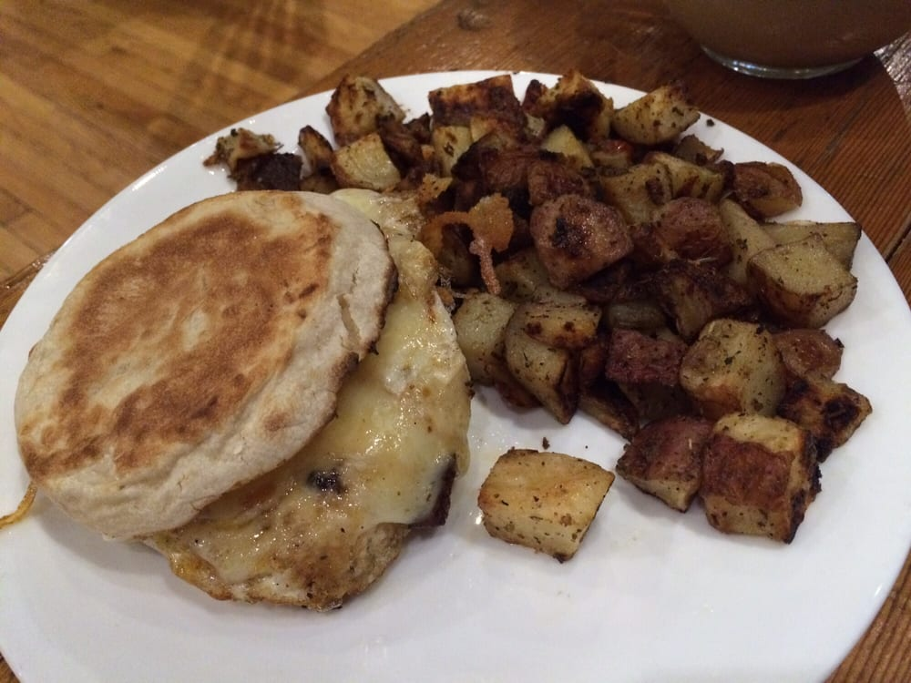 Classic breakfast sandwich with side of roasted potatoes ...
