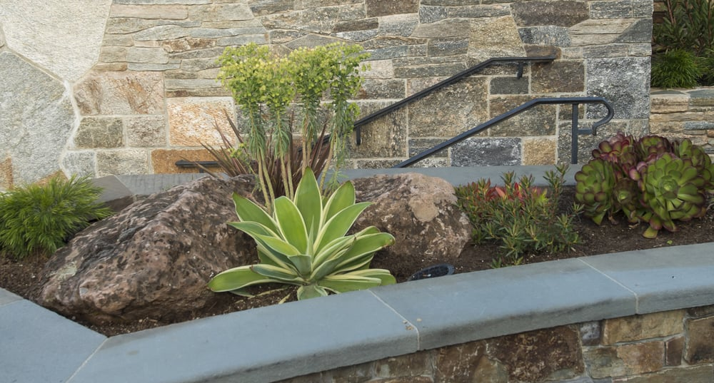 Natural Stone Retaining Wall With Bluestone Caps In Paved