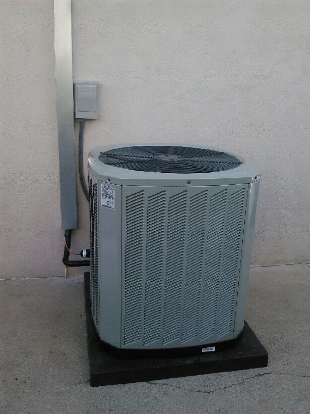 air conditioning unit outside installed on a pad and line